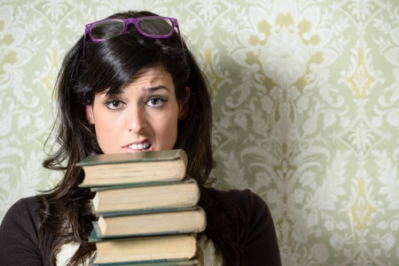 Upset female student holding old books on retro background before exam. Caucasian unhappy woman with glasses. photo