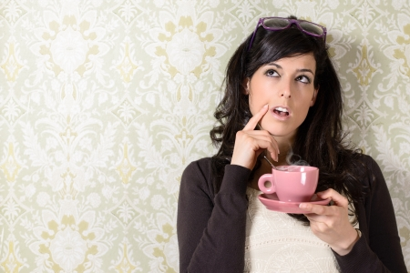 skeptic: Pensive woman thinking,  drinking hot steaming coffee and having an idea on retro background. Beautiful caucasian brunette woman wearing sweater and glasses.