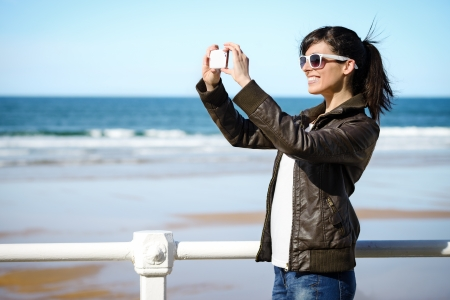 Joyful woman taking photo with cell phone on the beach on spring. Happy girl on vacation taking picture on sea background.