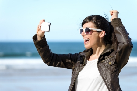 taking video: Fun woman video call on cell phone. Playful happy girl on vacations taking self photo on sea background at the beach. Stock Photo