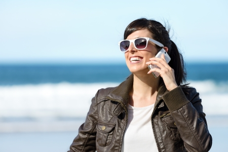 Woman talking on cell phone on sea background on spring sunny day. Happy beautiful caucasian girl talking by cellular outdoors. Copy space. photo