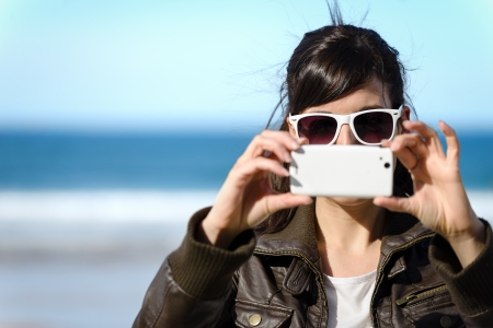 Woman taking photo with cell phone on the beach on spring. Happy girl on vacation taking picture on sea background.