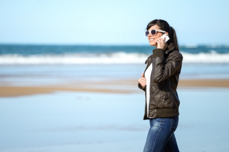 Casual woman talking on cellphone and walking on the beach on spring sunny day. Beautiful happy caucasian brunette model. photo