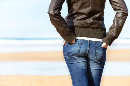 Casual woman with hands in jean pockets looking to the sea on beach. Sexy casual girl relaxing on holidays. Copy space.