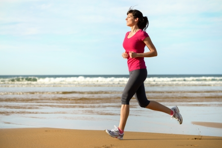 Woman running on beach at sunset. Beautiful fitness caucasian girl exercising outdoors on sea background. Caucasian fit model. photo
