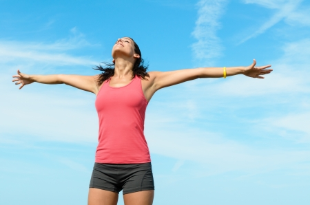 bliss: Happiness and bliss concept with beautiful woman raising arms to the blue sky on summer holidays. Beautiful caucasian sporty girl. Stock Photo