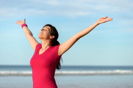arms raised: Blissful fitness woman raising arms to the sky on beach at sunset after working out. Happy female athlete feeling the breeze on sea background. Achievements and goals on sport concept.