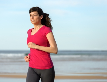 Woman running and exercising on beach at sunset. Brunette caucasian fitness girl jogging and working out outdoors. Copy space. photo