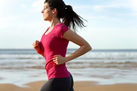 Woman running fast on beach at sunset. Brunette fitness girl runner exercising outdoors on sea background. Caucasian female athlete training.