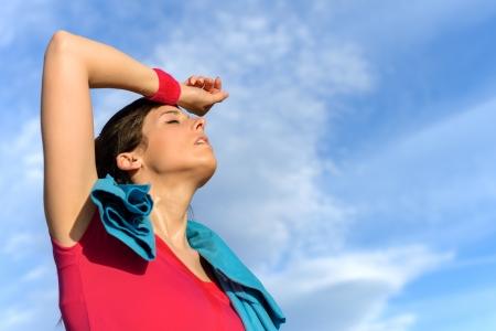 sudoracion: Fitness mujer sudorosa cansado después de entrenar. Sudoración caucásica atleta femenina y agotado después de hacer ejercicio en el fondo cielo copia espacio. Foto de archivo