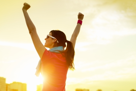achieve goal: Happy successful sportswoman raising arms to the sky on golden back lighting sunset summer. Fitness athlete with arms up celebrating goals after sport exercising and working out outdoors. Copy space.