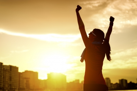 Deportista exitoso feliz levantando los brazos al cielo en luz dorada verano de nuevo puesta de sol. Aptitud atleta con los brazos para arriba celebrando goles después de hacer ejercicio y deporte al aire libre, hacer ejercicio. Copiar el espacio.