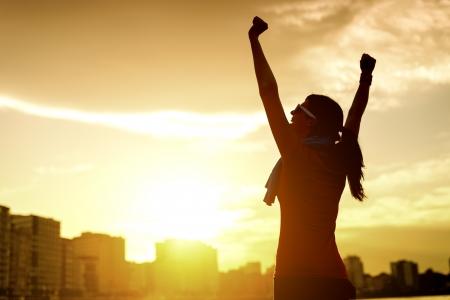 doelen: Happy succesvolle sportvrouw verhogen armen naar de hemel op gouden achtergrond verlichting zonsondergang zomer. Fitness atleet met armen omhoog vieren doelen na het sporten te oefenen en uit te werken buitenshuis. Kopieer de ruimte. Stockfoto