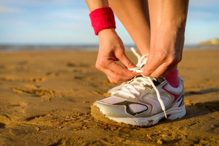 lace up: Running and jogging exercising concept  Woman tying laces before training on beach  Unrecognizable caucasian girl wearing sport shoes