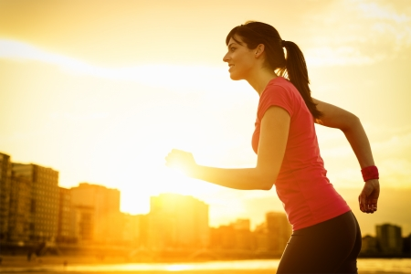 exercising: Woman running and exercising on beautiful golden summer sunset background on city beach  Female athlete fitness girl training  copy space