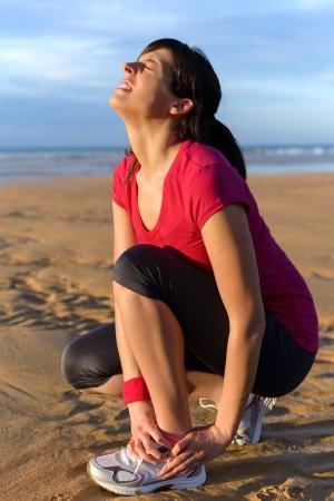 �jog: Mujer esguince de tobillo corredor joven mujer que sufre de una lesi�n en el tobillo durante el ejercicio corriente y mujer cauc�sica en la playa Foto de archivo