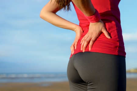 low back: Female athlete lower back painful injury  Caucasian fitness girl gripping her lowerback because sport injury after exercising and running