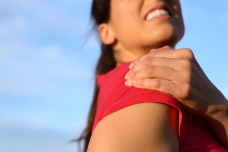 Fitness woman suffering from shoulder injury while exercising  Sky copy space background  photo