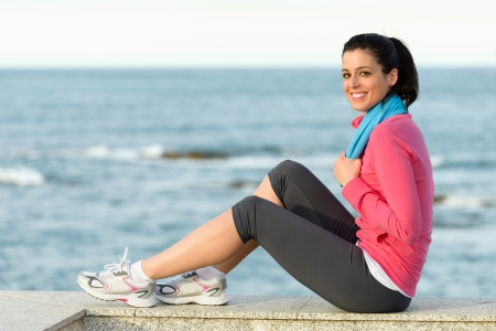 fits in: Beautiful fitness girl sitting and resting on sea background after exercising  Caucasian woman healthy lifestyle and relaxing  Copy space