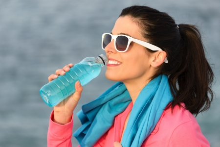 Fitness woman drinking and resting after training outdoors  Beautiful caucasian girl sitting and relaxing after exercising  Copy space  photo