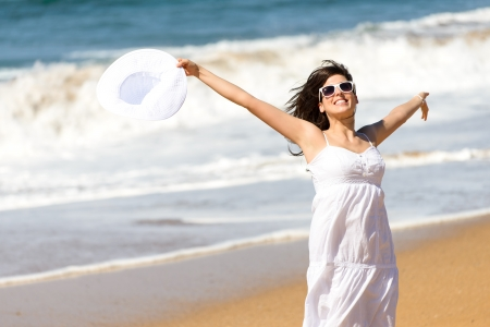 Playful happy woman jumping, running and dancing on beach  Happiness on summer vacation  Caucasian beautiful girl smiling and raising arms, holding white hat