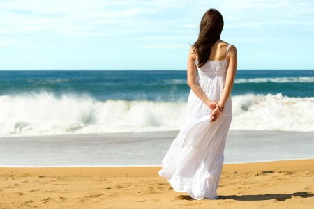 tranquil: Young brunette woman in summer white dress standing on beach and looking to the sea  Caucasian girl relaxing and enjoying peace on vacation  Stock Photo