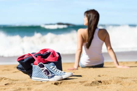 Summer scene and vacation on beach concept  Casual sneakers, sunglasses and handbag on foreground  Young woman sitting for relaxing and looking the sea and waves on background