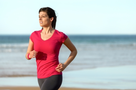 Woman running on beach in summer day at sunset.  Happy fitness girl exercising on sea background. Beautiful caucasian brunette model. Stock Photo - 19249794