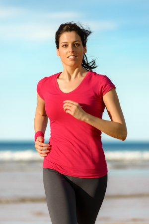 Woman running on beach in summer day at sunset.  Happy fitness girl exercising on sea background. Beautiful caucasian brunette model.