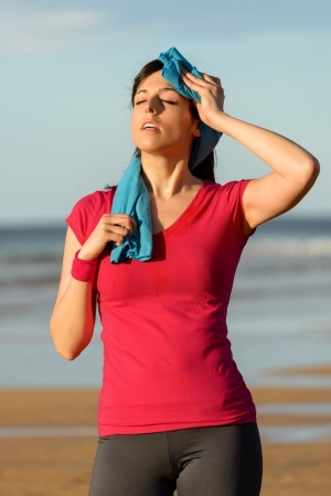 sweaty: Athlete woman wiping sweat from her forehead with a towel after running in summer on beach . Tired fitness girl sweating after exercising outdoors.