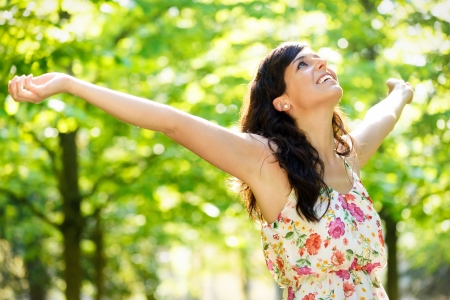 Carefree happy woman in spring or summer forest park raising arms with happiness, hope and vitality. Caucasian girl relaxing and enjoying life on nature outdoors.
