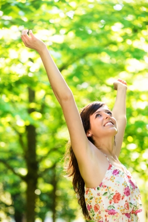 spring time: Happy young woman raising arms enjoying freshness of spring season in nature park surrounded by tress. Caucasian beautiful girl with open arms relaxing and celebrating life outdoors. Stock Photo