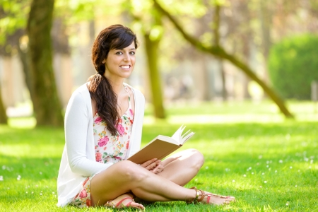 well read: Happy woman reading and holding  story book in fresh green park on spring or summer day  Caucasian brunette girl smiling and enjoying sitting on grass outdoors  Stock Photo