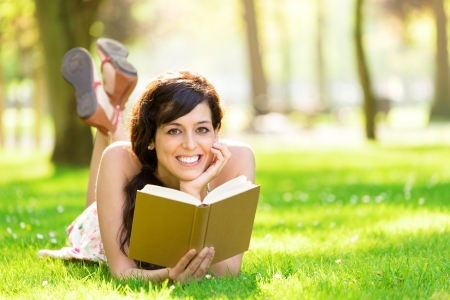 Happy woman reading and holding  story book in fresh green park on spring or summer  Caucasian brunette beautiful girl smiling and day dreaming lying down on grass outdoors  photo
