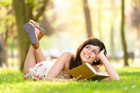 Happy woman reading and holding  story book in fresh green park on spring or summer  Caucasian brunette beautiful girl smiling and day dreaming lying down outdoors  photo