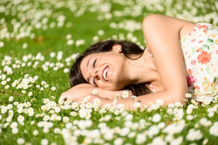 sleep well: Happy woman resting and relaxing lying down on grass surrounded by flowers on park outdoors. Beautiful woman with closed eyes in spring dress napping and day dreaming.