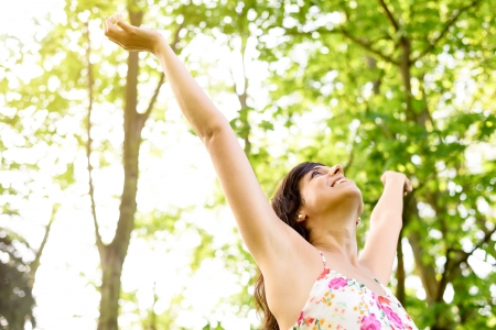 Happy and carefree woman raising arms  to the sky on fresh bright spring greenery. Caucasian beautiful girl happiness and relaxation on nature. Stock Photo
