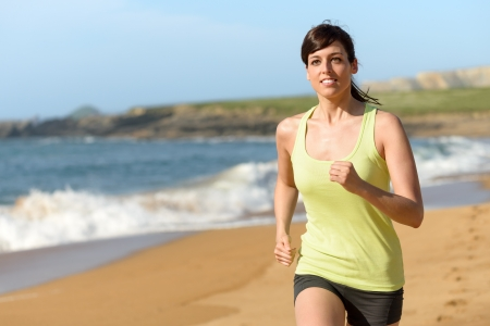 Woman running on beach in summer. Brunette female athlete exercising on nature. Sport girl training. Fitness caucasian model. Stock Photo - 19426698
