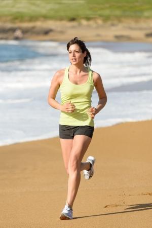 Woman running on beach in summer. Brunette female athlete exercising on nature. Sport girl training. Fitness caucasian model. Stock Photo - 19426696