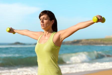 trabalhar fora: Mulher treinando ombros com halteres na praia. Ver�o trabalhar fora, fitness e exerc�cio com pesos ao ar livre. Menina esporte Caucasiano treinando duro.