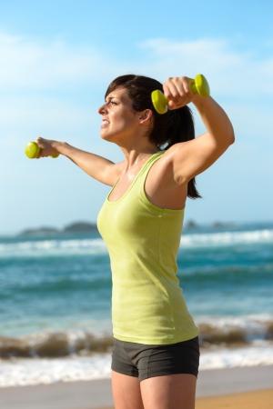 trabalhar fora: Mulher ombros de treinamento com halteres na praia. Ver�o trabalhar fora, fitness e exerc�cio com pesos ao ar livre. Caucasiano treino menina dif�cil.