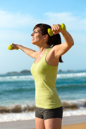 Woman training shoulders with dumbbells on beach. Summer work out, fitness and exercising with weights outdoor. Caucasian sport girl training hard. Stock Photo - 19426701