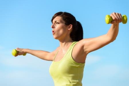 atmung: Frau Training mit Hanteln die Schultern am Strand. Sommer erarbeiten, Fitness und Training mit Gewichten im Freien. Europäischer Sport Mädchen hart trainiert.