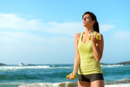 Fitness woman working out on beach in summer. Sporty girl training biceps hard with dumbbells. Sweaty sport caucasian female sportswoman. Stock Photo - 19457148
