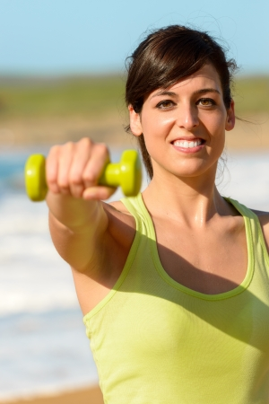 Fitness woman working out on beach in summer. Happy sporty girl lifting weights and punching outdoor. Caucasian sportswoman exercising. Stock Photo - 19458938