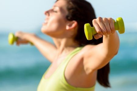 trabalhar fora: Mulher ombros de treinamento com halteres na praia. Ver Banco de Imagens
