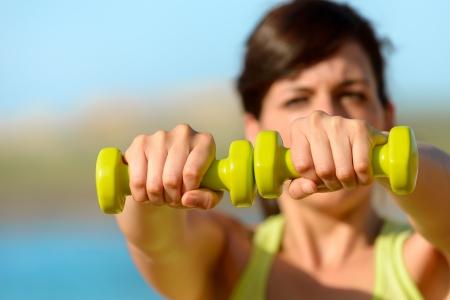 trabalhar fora: Mulher ombros de treinamento com halteres na praia. Ver�o trabalhar fora, fitness e exerc�cio com pesos ao ar livre. Caucasiano treino menina dif�cil. Copie o espa�o.