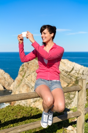 Tourist woman taking photo with cellphone and having fun on summer travel. Joyful brunette girl smiling and taking snapshot with phone on coast landscape. Asturias, Spain. photo