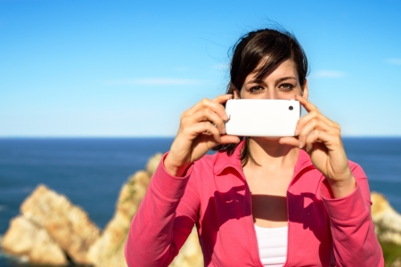 cellular telephone: Tourist woman taking photo with cellphone and having fun on summer travel. Brunette girl smiling and taking snapshot on coast landscape.