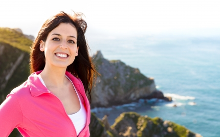 asturias: Woman smiling on nature coast landscape background. Happy beautiful brunette girl enjoying the view on summer travel in Asturias, Spain.